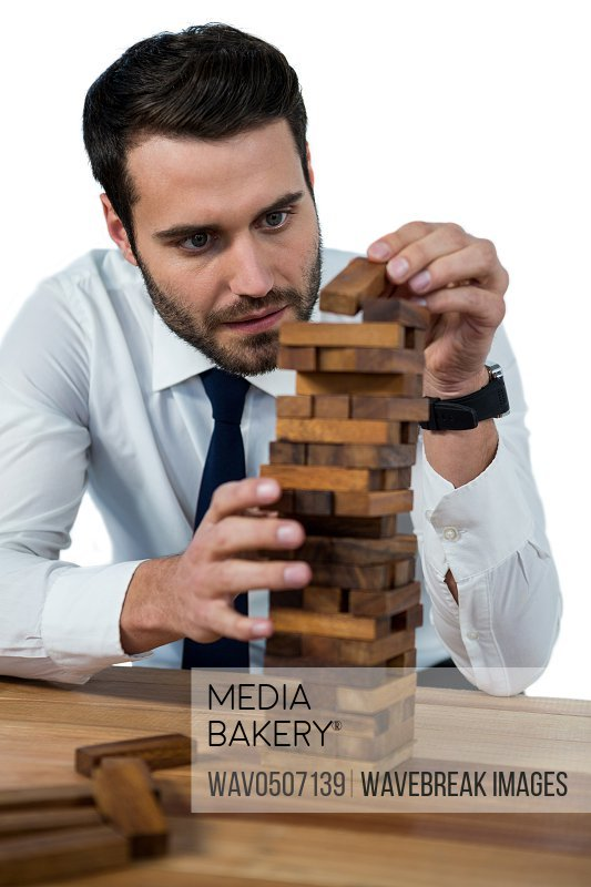 Businessman placing wooden block on a towerA�against white background