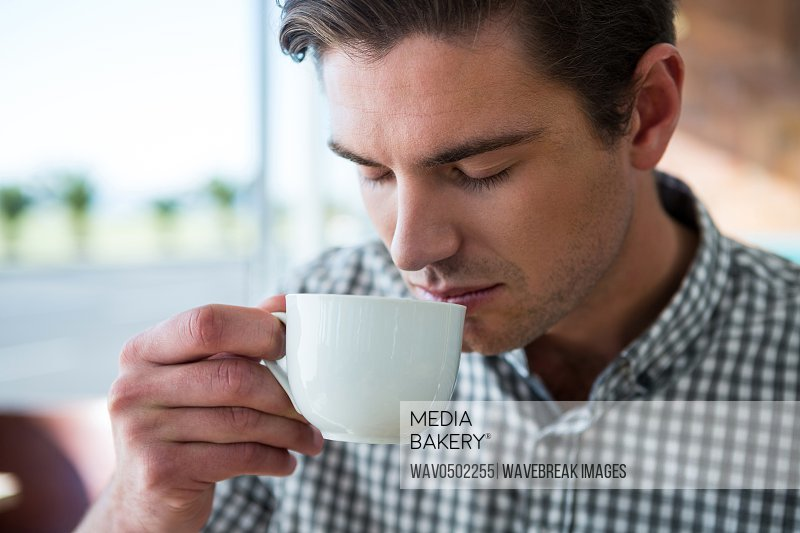 Close-up of a man having coffee in coffee shop