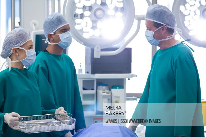 Surgeons interacting while performing operation in operation theater of hospital