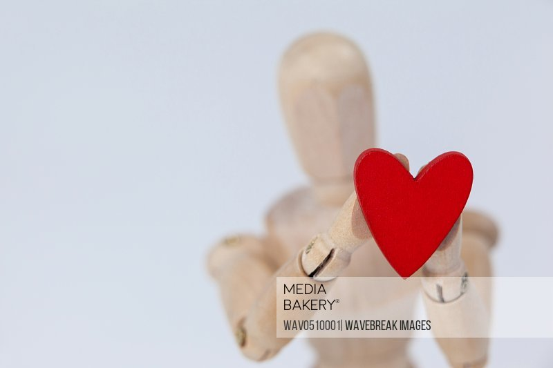 Wooden figurine holding a red heart against white background