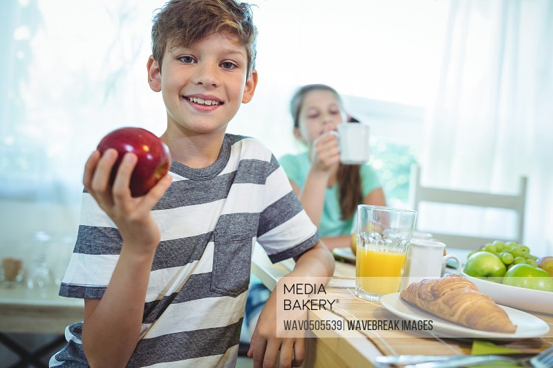 Smiling boy holding an apple at home