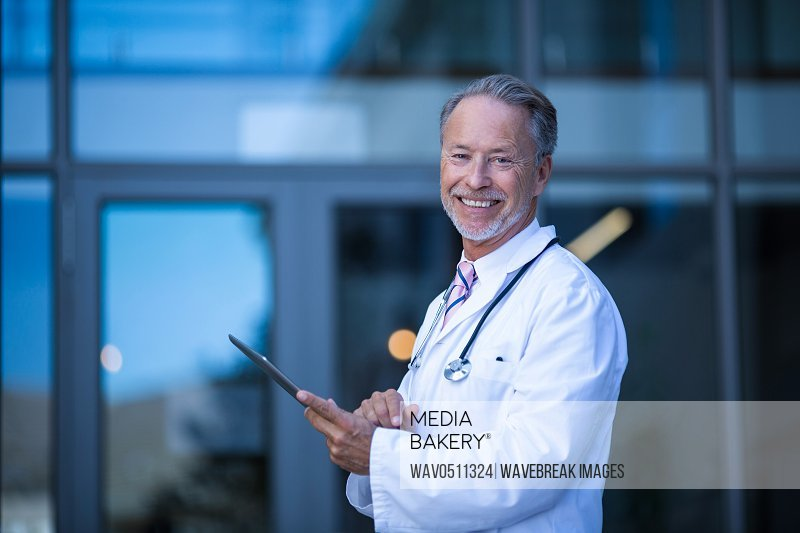 Portrait of male surgeon holding digital tablet at hospital