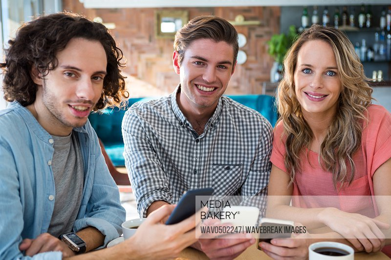 Portrait of smiling friends using their mobile phone in coffee shop