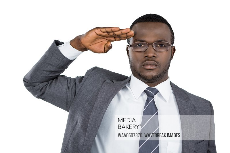 Close-up of businessman saluting against white background