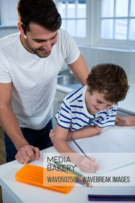 Father helping son with homework at home in the kitchen