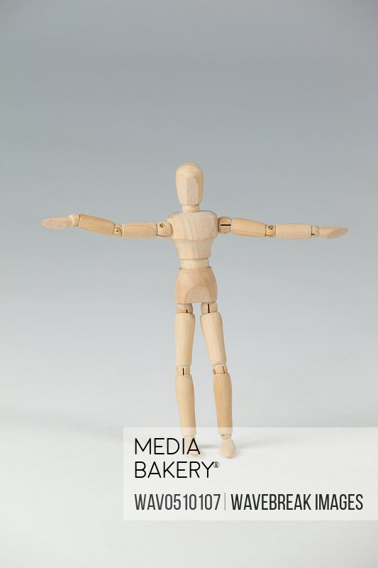 Wooden figurine standing with arms spread wide against white background
