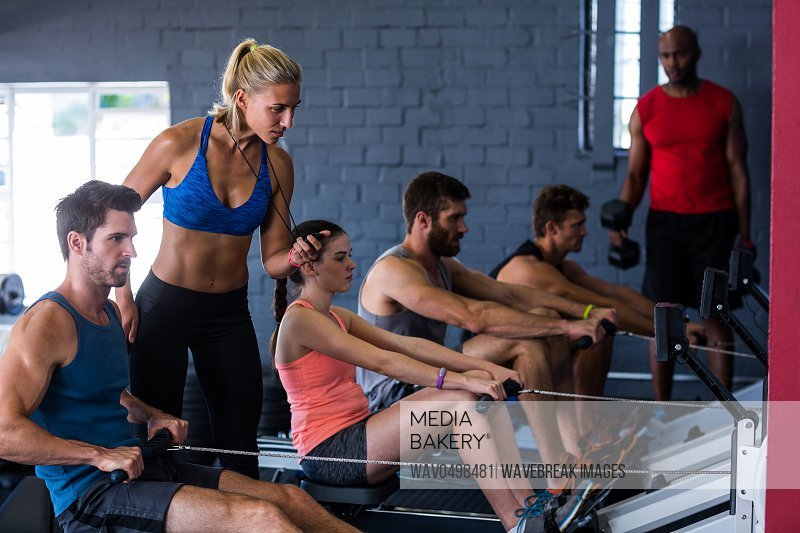 People using rowing machine with fitness instructor standing in gym