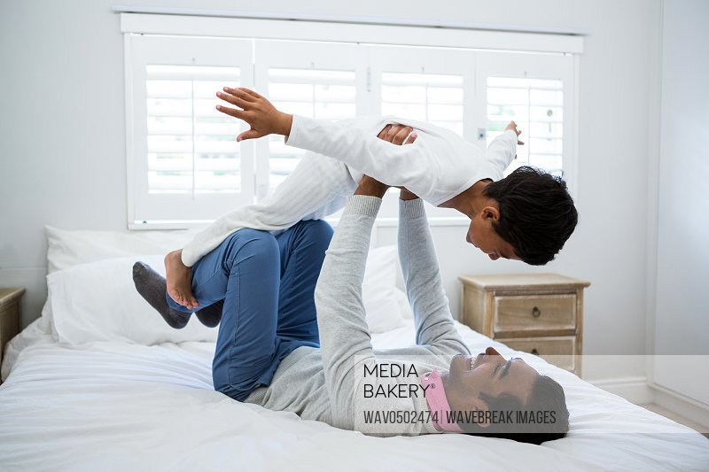 Father and son playing on bed in the bedroom