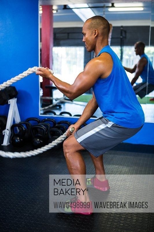 Side view of male athlete exercising with ropes in gym