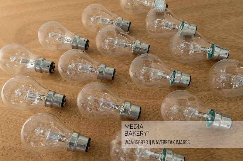Electric bulbs arranged on wooden plank