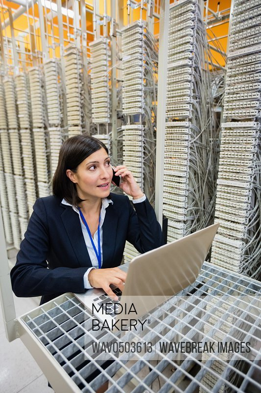 Technician talking on mobile phone while using laptop in server room