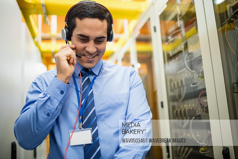 Technician talking on head phones while working in server room