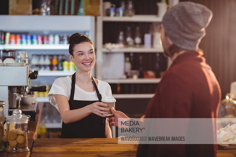 Waitress offering a cup of coffee in cafe