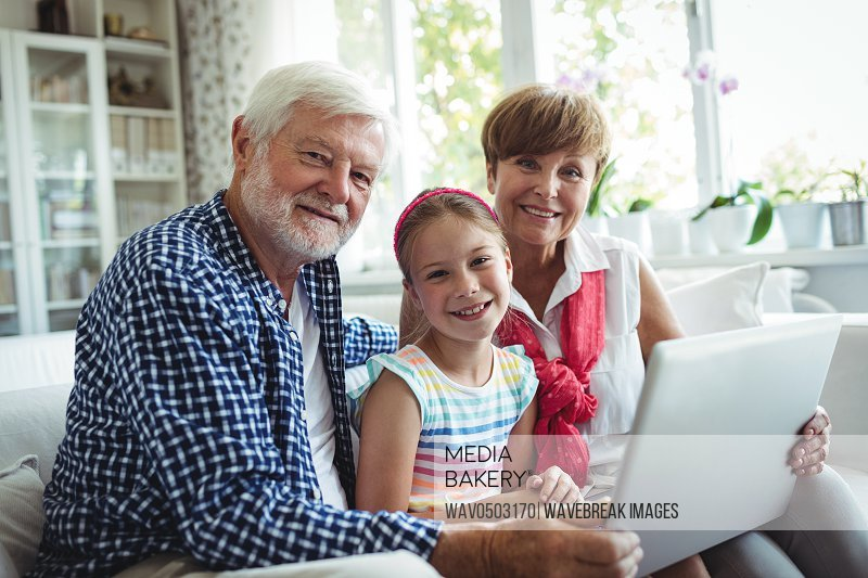 Portrait of grandparents and granddaughter using laptop in living room in living room at home