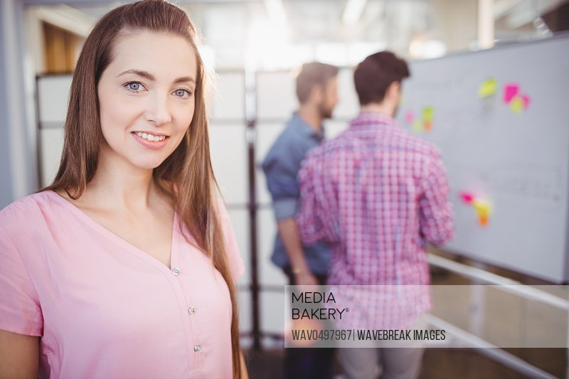 Portrait of beautiful young female executive standing creative office