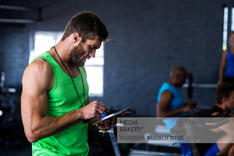 Hipster man using tablet while standing in gym
