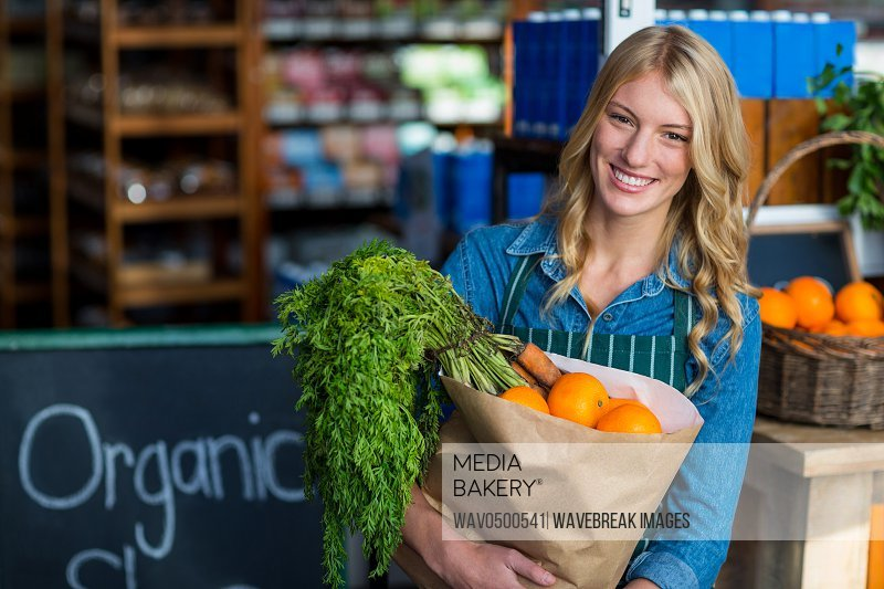 Portrait of smiling woman holding a grocery bag in organic section of supermarket