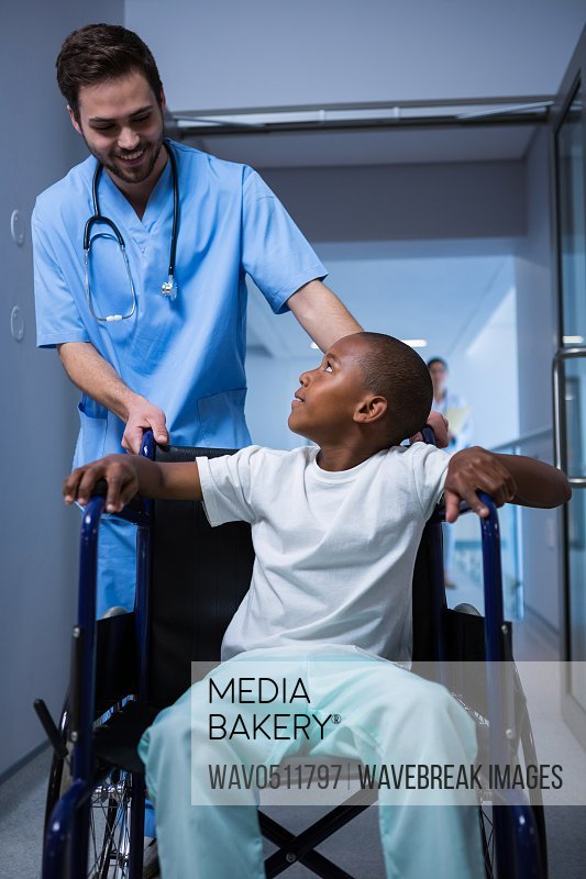 Male nurse interacting with child patient in corridor at hospital