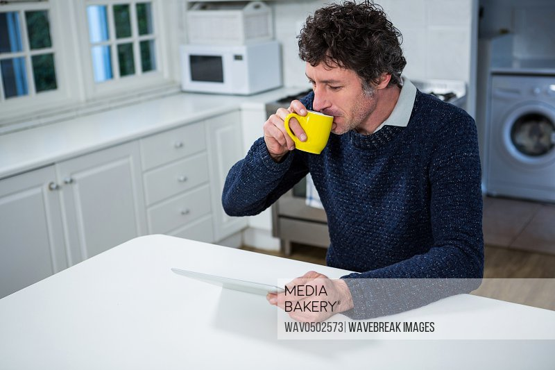 Man using digital tablet while having coffee in the kitchen