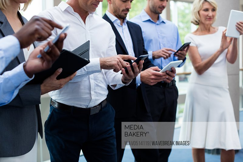 Business executives using digital tablet and mobile phone