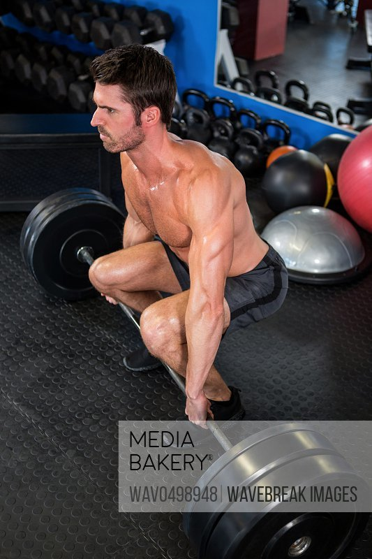 Shirtless man lifting barbell in fitness studio