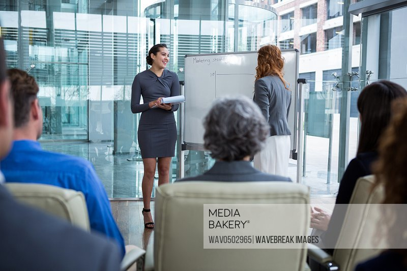 Businesswomen discussing on white board with coworkers in office