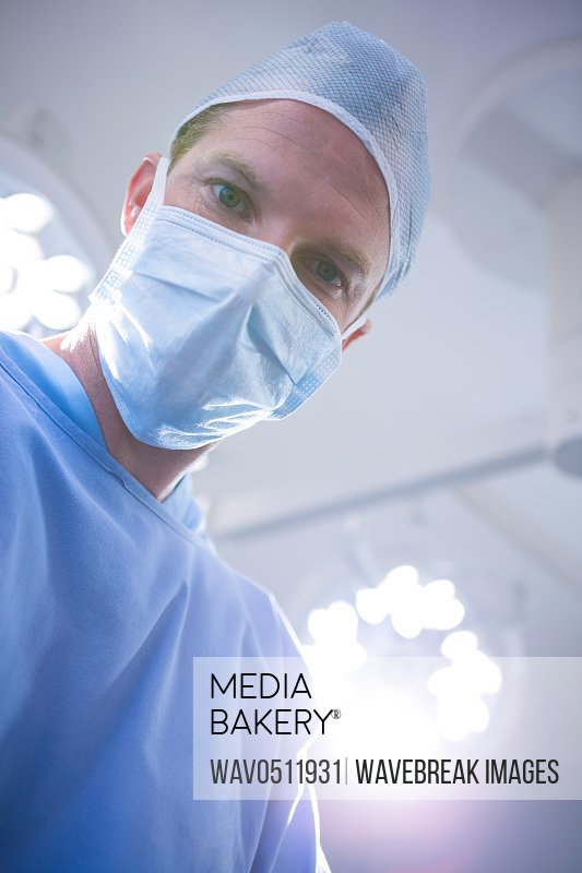 Male surgeon wearing surgical mask in operation theater