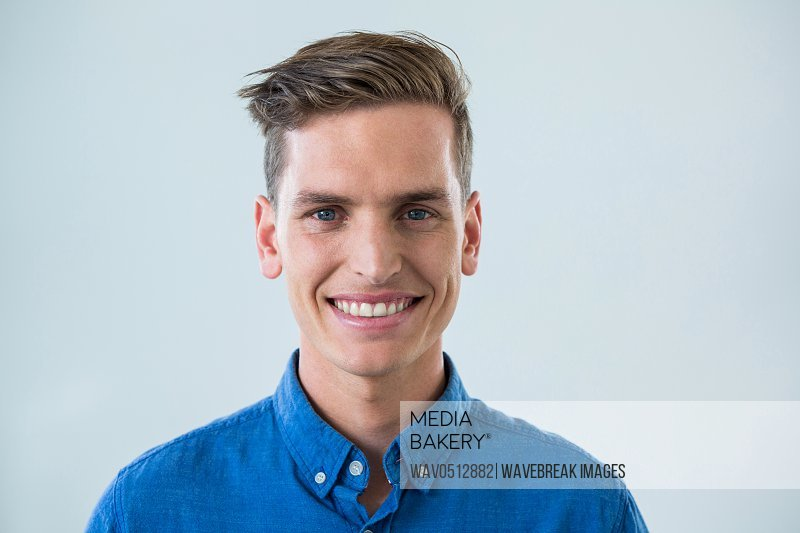 Portrait of smiling man in blue shirt against white background