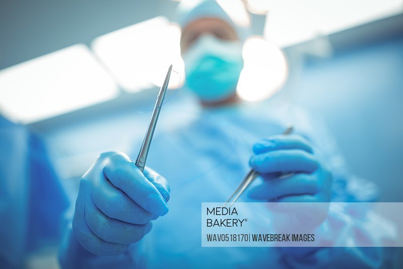 Surgeon holding surgical tools in operation theater