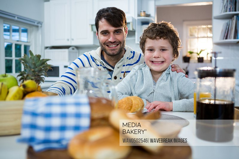 Portrait of father and son having breakfast in the kitchen at home