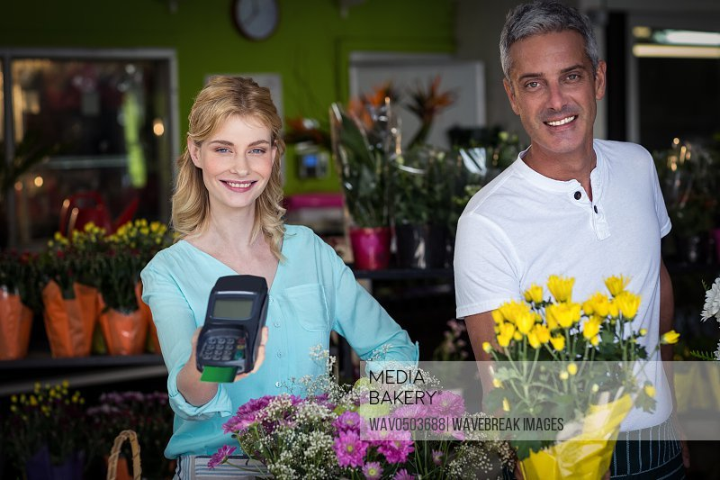 Portrait of smiling florist showing credit card terminal in flower shop