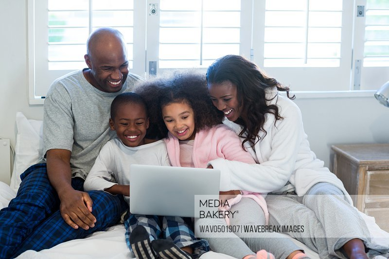 Family using laptop on bed at home