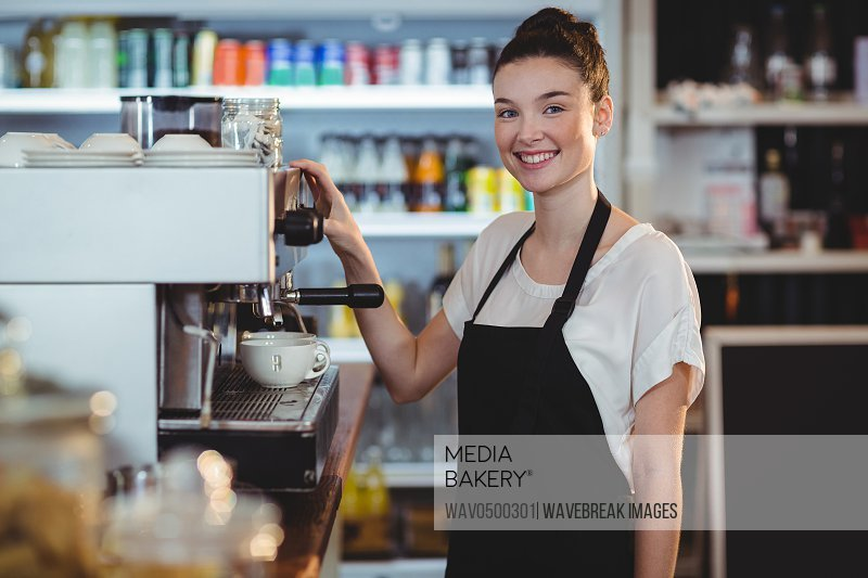 Smiling waitress making cup of coffee in cafe