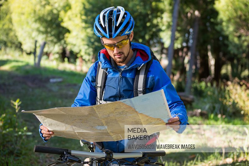 Male mountain biker looking at map in the forest