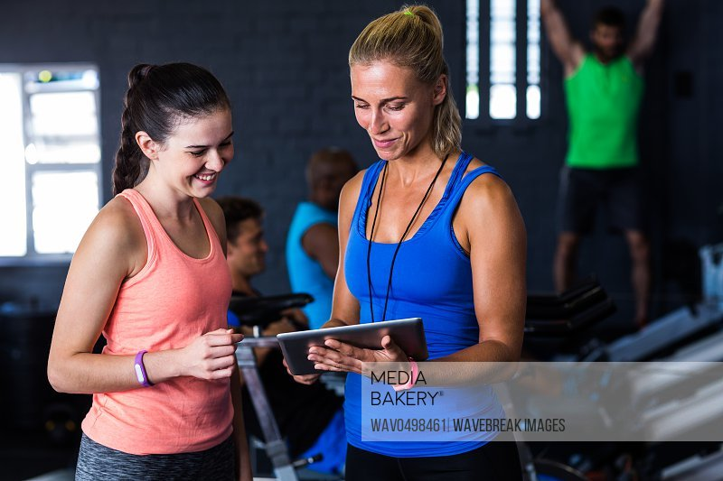 Smiling friends with digital tablet while standing in gym