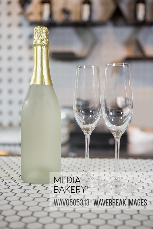 Champagne bottle and champagne flute on bar counter in bar