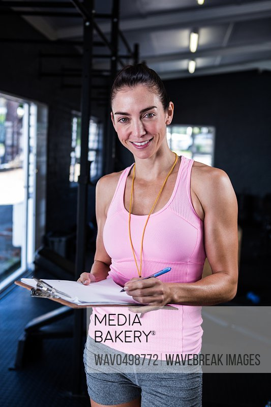 Portrait of happy fitness instructor holding clipboard in gym