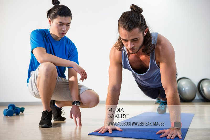 Fitness instructor helping fitness man with push-up in gym