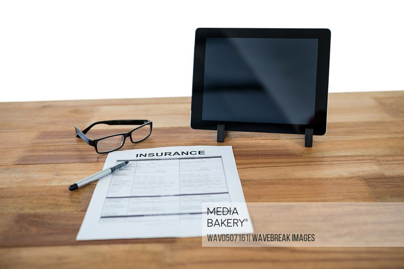 Digital tablet insurance form spectacle and pen on desk against white background