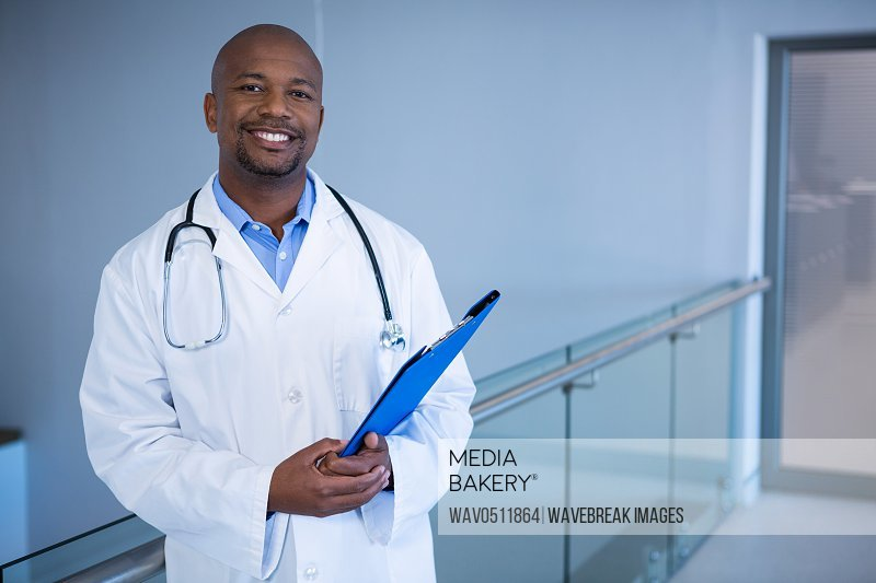 Portrait of male doctor standing with clipboard in corridor at hospital