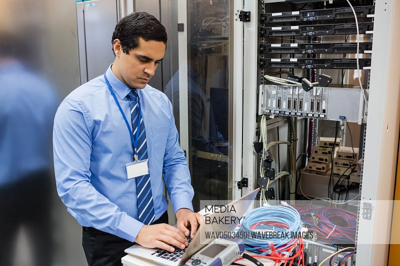 Focused technician working on laptop in server room