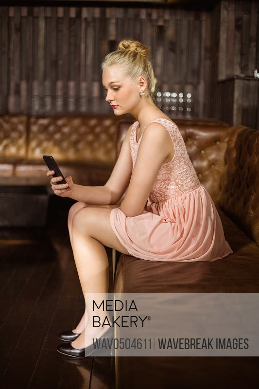 Beautiful woman sitting on sofa and using mobile phone at bar