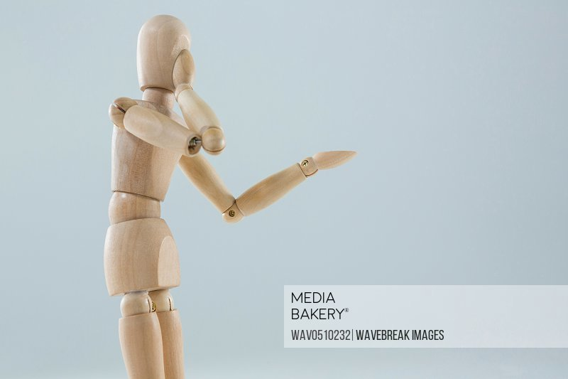 Wooden figurine applying makeup against white background