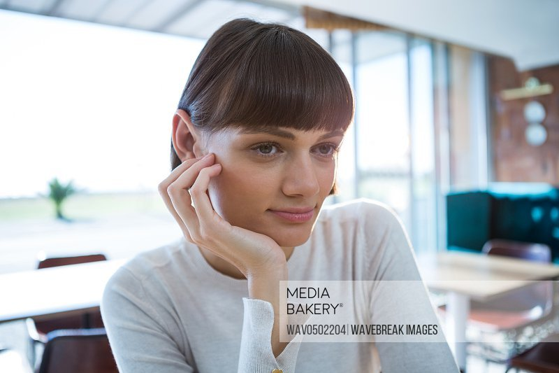 Thoughtful woman sitting in cafeteria