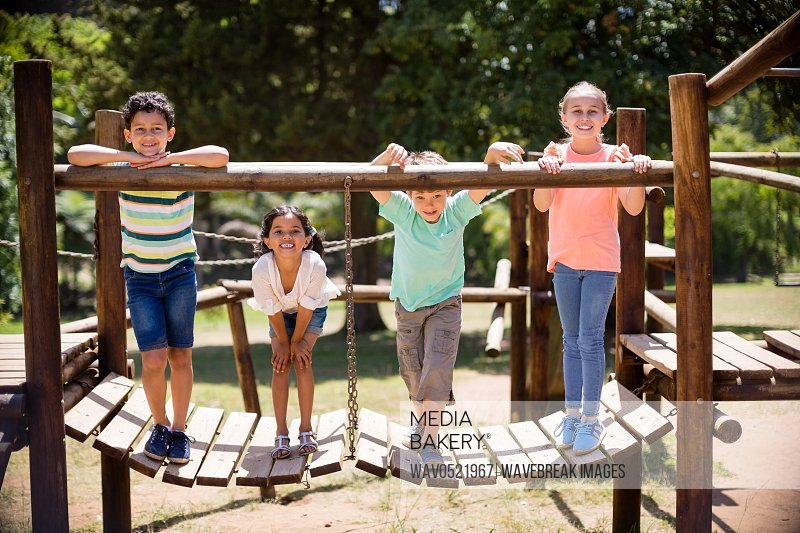 Kids standing and smiling on a playground ride in park