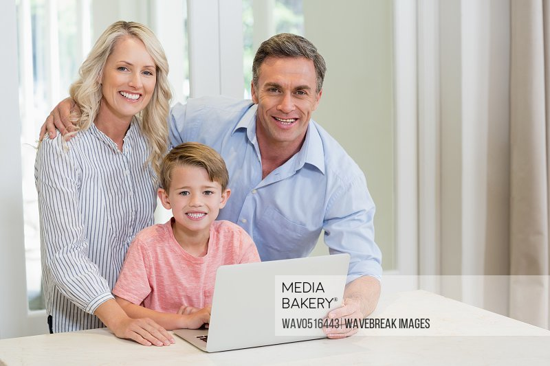 Parents and son using laptop at home