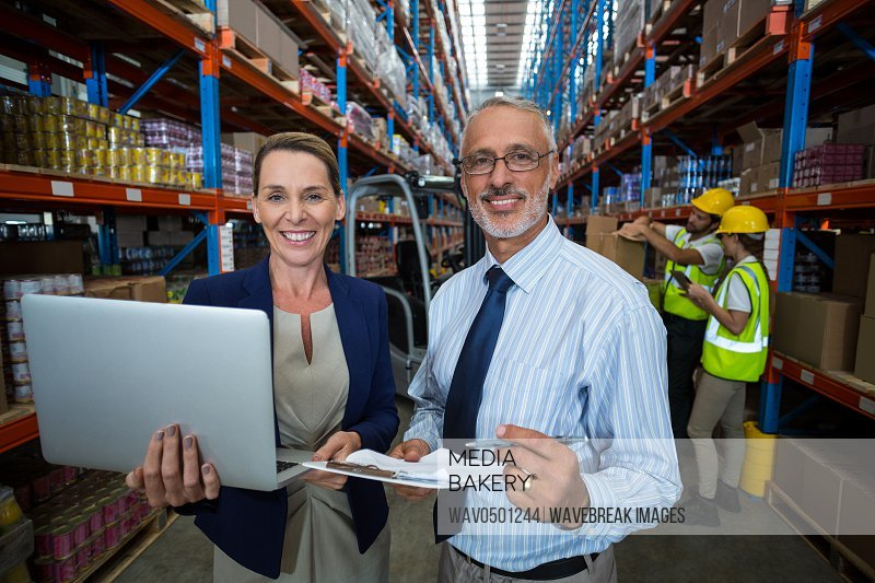Warehouse manager and client holding digital tablet and clipboard in warehouse