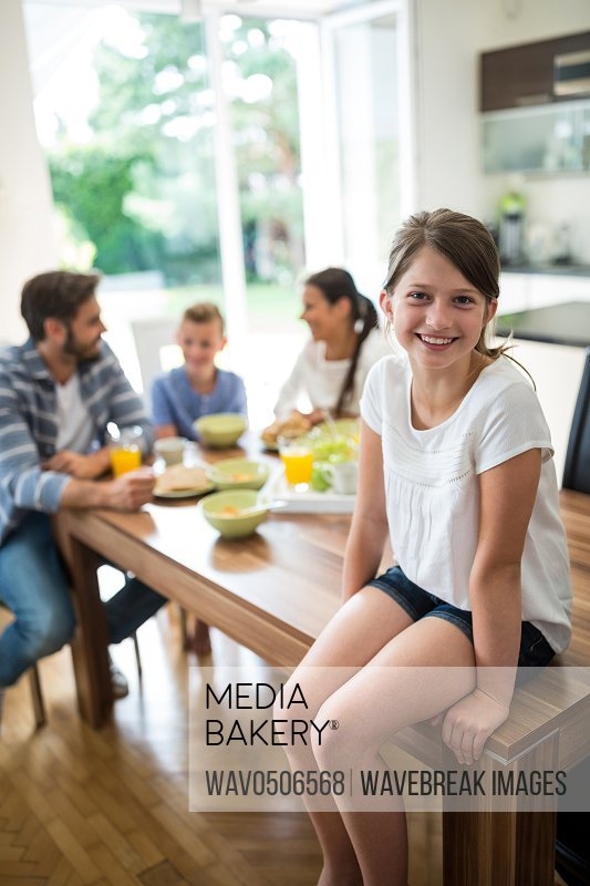 Portrait of girl sitting on dining table while family having breakfast in background at home