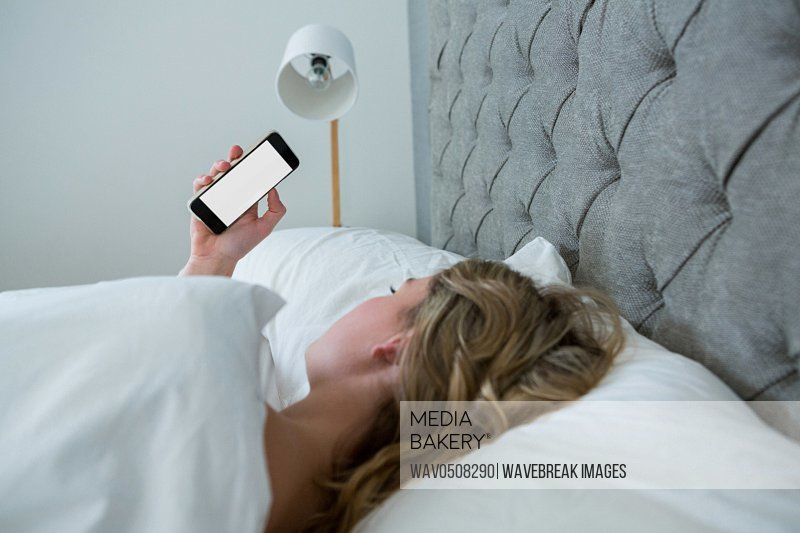 Young woman looking at mobile phone while sleeping