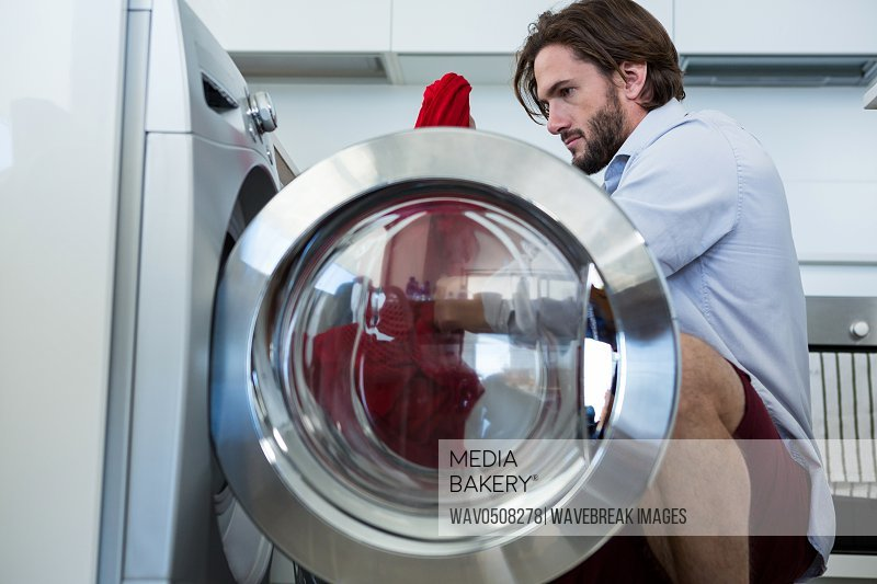Man putting his clothes into washing machine at home